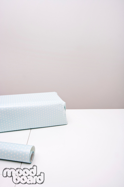 Gift box and wrapping paper on table against gray background