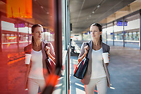 Portrait of young attractive businesswoman holding cup of coffee while walking