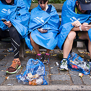 November 1, 2015 - New York, NY : Runners use their cell phones as they sit on benches along Central Park West after participating in the 2015 TCS New York City marathon on Sunday.<br />  CREDIT: Karsten Moran for The New York TImes