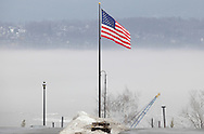An American flag flies on the Newburgh waterfront above the Hudson River, which is party covered in fog on a warm winter day. Jan. 2, 2010. The City of Beacon is visible on the east side of the river.
