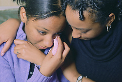 Teenage girl crying; being comforted by older sister,