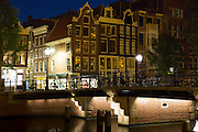 Night scene shops and silhouettes of bicycles on bridge, Singel Canal in Nine Streets area, Amsterdam, Holland