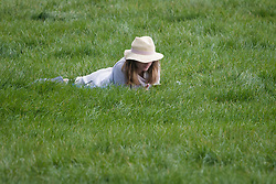 © Licensed to London News Pictures. 08/04/2020. London, UK. A woman lying down on Primrose Hill in North London, during a pandemic outbreak of the Coronavirus COVID-19 disease. The public have been told they can only leave their homes when absolutely essential, in an attempt to fight the spread of coronavirus COVID-19 disease. Photo credit: Ben Cawthra/LNP