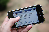 Close-up of a person using Facebook on an iPhone
