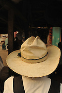 A straw, wide-brimmed cowboy hat from the back, on a farmer in Ixcan, Guatemala - a dusty, rough border town near the Mexican border.