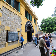 Visitors stand outside the main entrance to Hoa Lo Prison. At right, a local tries to sell souvenirs to the tourists. Hoa Lo Prison, also known sarcastically as the Hanoi Hilton during the Vietnam War, was originally a French colonial prison for political prisoners and then a North Vietnamese prison for prisoners of war. It is especially famous for being the jail used for American pilots shot down during the Vietnam War.