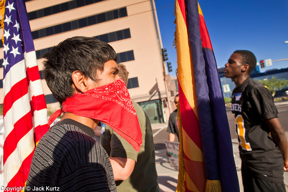 "22 OCTOBER 2011 - PHOENIX, AZ:    Occupy Phoenix protesters wait to cross a street during a march through Phoenix Saturday. The demonstrations at Occupy Phoenix, AZ, entered their second week Saturday. About 50 people are staying in Cesar Chavez Plaza, in the heart of downtown. The crowd grows in the evening and on weekends. Protesters have coordinated their actions with police and have gotten permission from the city to set up shade shelters and sleep in the park, but without tents or sleeping bags, which is considered ""urban camping,"" instead protesters are sleeping on the sidewalk.    PHOTO BY JACK KURTZ"