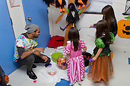 Middletown, New York  - Young girls wearing costumes play a fishing game while a volunteer looks on during the Halloween Fall Festival at the Middletown YMCA Center for Youth Programs on Oct. 26, 2013.