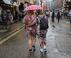 Portland Place, London, June 25th 2016. Thousands of LGBT people and their supporters gather for Pride in London, a colourful celebration of the hard-won rights of lesbian, gay, bisexual and transgender  people. PICTURED: Two women walk through the rain in Soho.