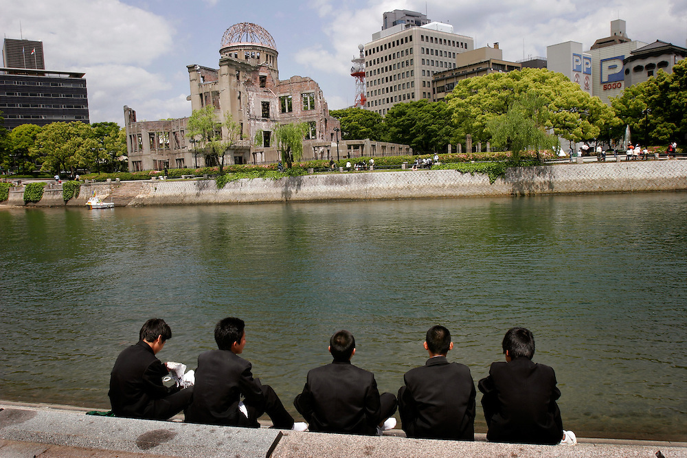 Schoolboys sitting at a riverbank inside the Peace Memorial Park, in front of the remains of the A-bomb Dome in Hiroshima