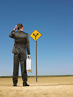 Businessman looking at road sign in desert back view