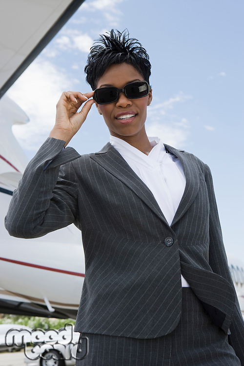Mid-adult businesswoman in sunglasses standing in front of private plane, low angle view.