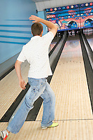 Young man bowling back view