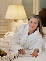 Woman wearing bathrobe writing lying on bed portrait