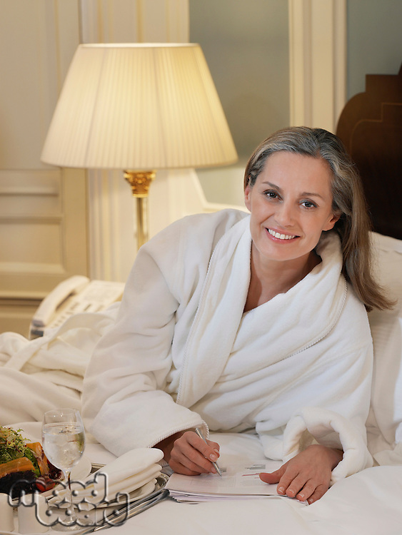 Woman wearing bathrobe writing lying on bed portrait