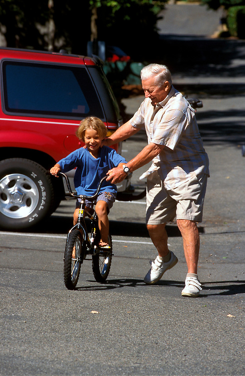 James Aikins helps his grandson James to learn how to ride a bike without training wheels. MR