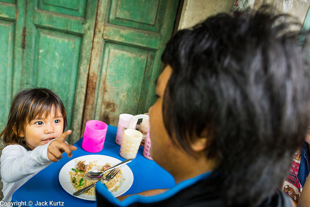 18 SEPTEMBER 2013 - BANGKOK, THAILAND: A girl and her father eat at a noodle stand in the Chinatown section of Bangkok. Thailand in general, and Bangkok in particular, has a vibrant tradition of street food and eating on the run. In recent years, Bangkok's street food has become something of an international landmark and is being written about in glossy travel magazines and in the pages of the New York Times.      PHOTO BY JACK KURTZ
