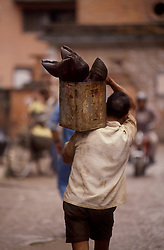 KATHMANDU, NEPAL - OCTOBER 1992 - A man carries a can full of animal hooves through the streets of Kathmandu. (PHOTO © JOCK FISTICK)