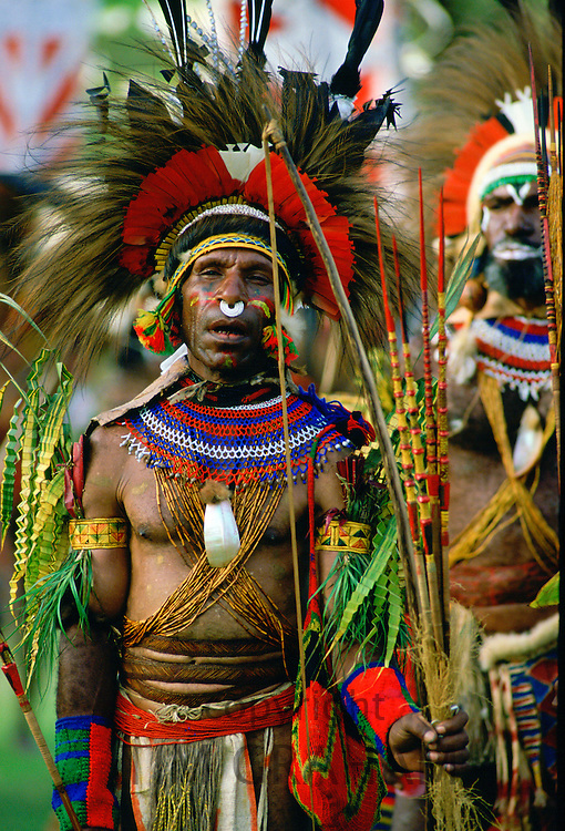 Tribesman with war paint, feathered headdress and bow and arrow at gathering of tribes at Mount Hagen in Papua New Guinea