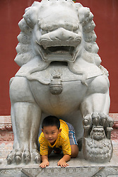 Boy climbs through large stone lion in Beihai Park in Beijing