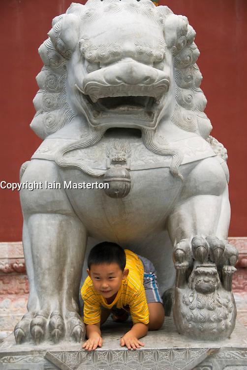 Boy climbs through large stone lion in Beihai Park in Beijing