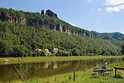 Radlerin auf Bank, Schrammsteine, Elbe bei Bad Schandau, Elbsandsteingebirge, Sächsische Schweiz, Sachsen, Deutschland.|.Scheammsteine over river Elbe near Bad Schandau, Saxon Switzerland, Saxony, Germany