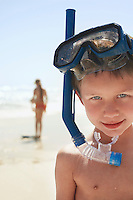 Boy (5-6) in snorkel on beach close-up portrait