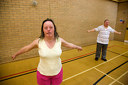 Day service users with learning disability doing arm warm up exercises in the gym,