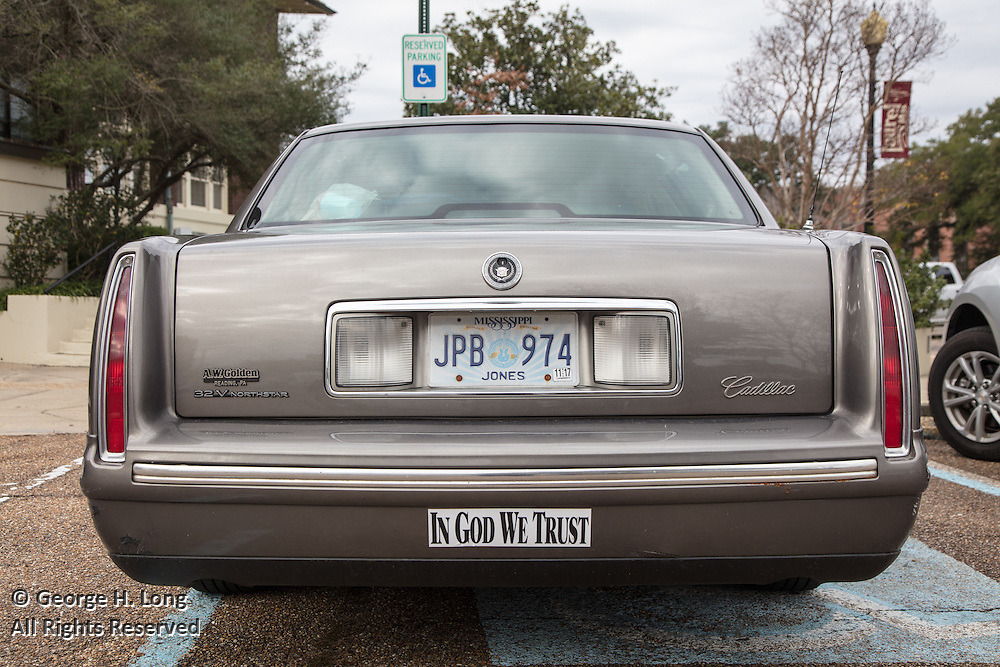 a champagne colored Cadillac with Jones County Mississippi license plate and a bumper sticker 'In God We Trust' outside the courthouse in Laurel, Mississippi