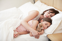 Mother and daughter sleeping in bed portrait