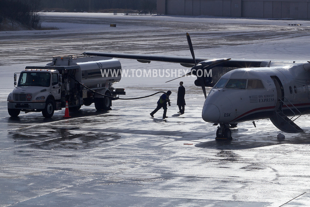 New Windsor, New York - A worker carries a fuel line to a US Airways Express-Piedmont DeHavilland DHC-8 Dash 8 Turboprop at Stewart International Airport on Jan. 26, 2013.