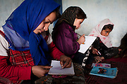 Afghanistan: Daughters Latifa (11 years) and Sameena (10 years old), study with a friend at their Mothers home in an abandoned building, at Tamil Mill Bus site in Kabul...Mariam supports her children by making between 20-30 pieces of 'bolony', the basic bread dish, with spinach/onion filling every morning at 09.00am. The 'bolony' is then taken to the city center by her eldest son Kadir, 13 years old. Each piece of bread sells for 5 Afs. (US$0.10c)..Mariam says she keeps the children from going to school in the winter because there is no heating at the school. Originating from Kabul, She says they fled to Iran for 6 years during the fighting with the Taliban, returning from Iran in 2001/02. Her husband was killed by a bomb blast in the city 7 years ago...Afghans returning from exile abroad face many challenges. Security is a major obstacle to return in many districts. Others choose not to return tot heir villages because of landlessness or the lack of job opportunities, fuelling population movements and especially further urbanisation. Impoverished returnees and IDP's living in Kabul cit struggle to meet their daily needs. The attraction of daily wage labour draws growing numbers tot he city. But the rising cost of rental accommodation and basic commodities price them out of the market and relegate them to life in the informal settlements which have mushroomed across the city...While 70-80% of kabul city os considered as 'informal' in the sense it is not covered by the Kabul Master Plan, UNHCR's focus is on a limited number of highly documented such 30 sites dotting the city which are home to over 2,000 families. Some families are living under canvas and the constant threat of eviction. others have gained a toe-hold in abandoned around building in the city...Afghanistan/UNHCR/Jason Tanner/February 2011