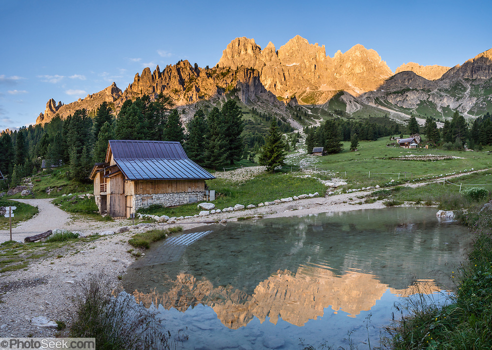 Sunrise reflects the Rosengarten/Catinaccio group in a pond. From Pera di Fassa village (in Pozza di Fassa comune in Val di Fassa), in Trentino-Alto Adige/Südtirol region, Italy, take a bus or lift to visit Rifugio Gardeccia Hutte and hike in the Rosengarten mountain massif (Catinaccio Group) of the Dolomites. 200 million years ago, Triassic coral reefs fossilized into Dolomite. Collision of tectonic plates lifted the Dolomites within the Southern Limestone Alps. UNESCO honored the Dolomites as a natural World Heritage Site in 2009. This panorama was stitched from 4 overlapping photos.