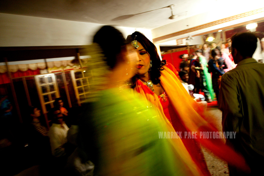 Hijras (eunuchs), arrive in colourful garbs at an underground party, June 16, 2005, Rawalpindi, Pakistan.  The suspected hideout of Osama Bin Laden, Al Qaeda leaders and countless Islamic militants, Pakistan is also home to one of the subcontinents largest communities of transsexuals, eunuchs and transvestites, or as they are more commonly known - Hijras. Caught between modernity and fundamentalism at the frontline in the war against terror, the Islamic Republic is a country at war with its own identity, yet its Kushras (Urdu for eunuch) stand out as a tight-nit community of devout Muslims. As Pakistan's most marginalised community, they live in fear ?24 hours a day?, according to the group She-male Rights of Pakistan. Hijras are considered by many as unclean, amoral, drug users, and who also have the ability to place curses. (Photo by Warrick Page)