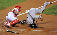 Nick Swisher gets upended during a play at the plate as Phillies catcher Chico Ruiz hangs onto the baseball during the 2009 World Series.