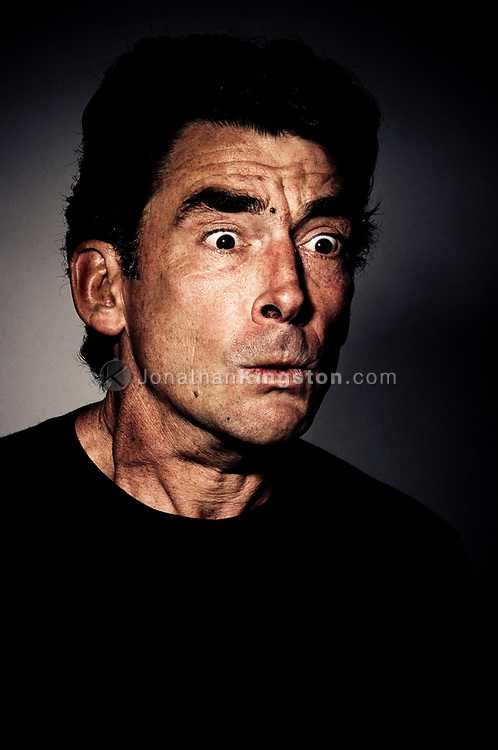 Low angle, close up, front view of a mature man in a dark t-shirt with a astonished look on his face.  Studio shot against a dark background. (releasecode: jk_mr1025) (Model Released)