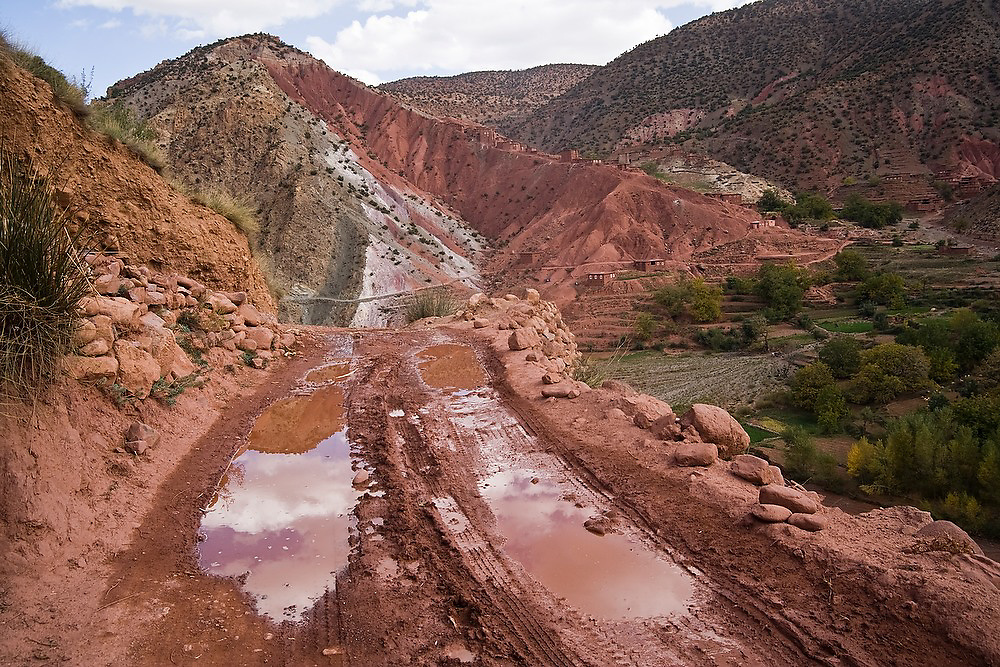 Water puddles form in the deep ruts of a muddy dirt road at Sebt Ait Bou Wlli in the M'Goun Massif, Central High Atlas, Morocco.
