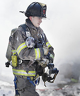 South Blooming Grove firefighter Erik Vath carries a dog away from a fire at 7 Wildwood Trail in Mountain Lodge Park on Wednesday, Feb. 13, 2013.
