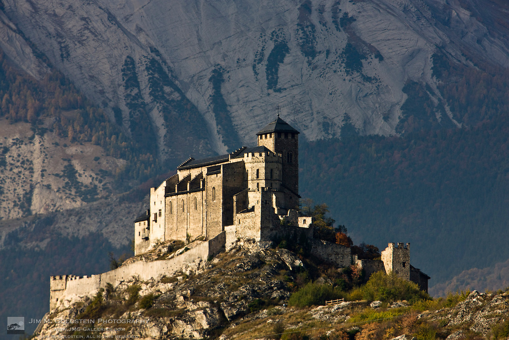 Castle Château De Valère  otherwise known as the Basilique de Valère with snow covered mountains in the background - Sion, Switzerland