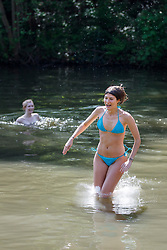 © Licensed to London News Pictures. 06/05/2018. London, UK. Jessica Iachia jumps in Hampstead Heath Mixed Bathing Pond in north London as temperatures hit 27C on Sunday, May 6, 2018. Photo credit: Tolga Akmen/LNP