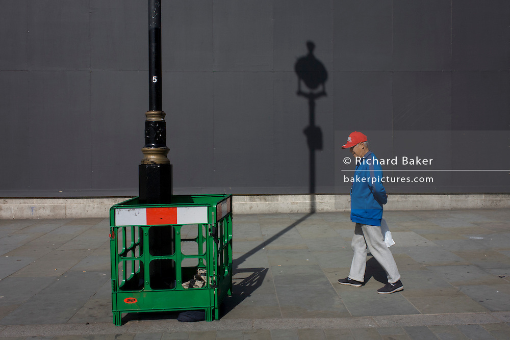 Tourist in red cap with a lamp post shadow against a grey construction hoarding in central London's Trafalgar Square.
