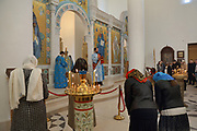 Worshippers bowing their heads at Sunday service in the narthex of the Cathedrale de la Sainte-Trinite de Paris, or Holy Trinity Cathedral of the Russian Orthodox Church, built 2013-16, on Quai Branly, in the 7th arrondissement of Paris, France. This room is plastered and lined with frescoes on a gold background, centred around the iconostasis. On the left is a manoualia, a large brass candle holder. The cathedral is part of a complex with the Centre Spirituel et Culturel Orthodoxe Russe, promoting Russian cultural religious heritage. Picture by Manuel Cohen