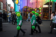 Volunteers for the cancer research charity Macmillan walk through Leicester Sq wearing wigs and holding green balloons.