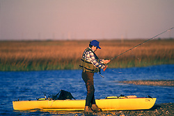 Stock photo of a man standing on shore and fly fishing beside his kayak