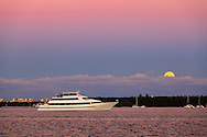 A motor yacht with a deck full of passengers cruises through Miami harbor towards southern Biscayne Bay and the Atlantic Ocean, as the full moon rises over Virginia Key in the background.<br />