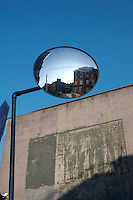 Buildings reflected in circular traffic mirror in Dublin Ireland