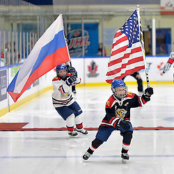 WHITBY, - Dec 17, 2015 -  Game #10 - United States vs. Russia at the 2015 World Junior A Challenge at the Iroquois Park Recreation Complex, ON.  Players from the Whitby Wildcats carry the team flags prior to the game.<br /> (Photo: Shawn Muir / OJHL Images)