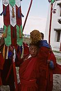 Mongolia. Maidar Buddhist ceremony  Erden Zuu, Karakorum      /  Procession boudhiste du Maidar.  (Monastère de Erdeni Zuu à Qaraqorin (Karakorum) Mongolie ),Pause . Le cortège s'est arrêté à un endroit aménagé pour la pause. Le haut dignitaire religieux local a une chaise, tandis que le lama commun est assis sur un tapis au sol. Un jeune moinillon de service distribue du thé au lait salé à ses supérieurs. /  100       P0007412