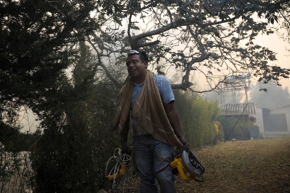 Un hombre llora mientras sostiene lo que pudo recuperar de su casa que quedo completamente quemada en el poblado de Zámbiza. Durante una sequía de dos meses, aproximadamente 2565 incendios forestales, (muchos presuntamente provocados) quemaron 3796 hectareas de bosques, algunas casas y muchos animales silvestres en las laderas boscosas que rodean Quito, la capital del Ecaudor.   Ningún humano murió, pero tomaran décadas antes de que las áreas afectadas se recuperen.