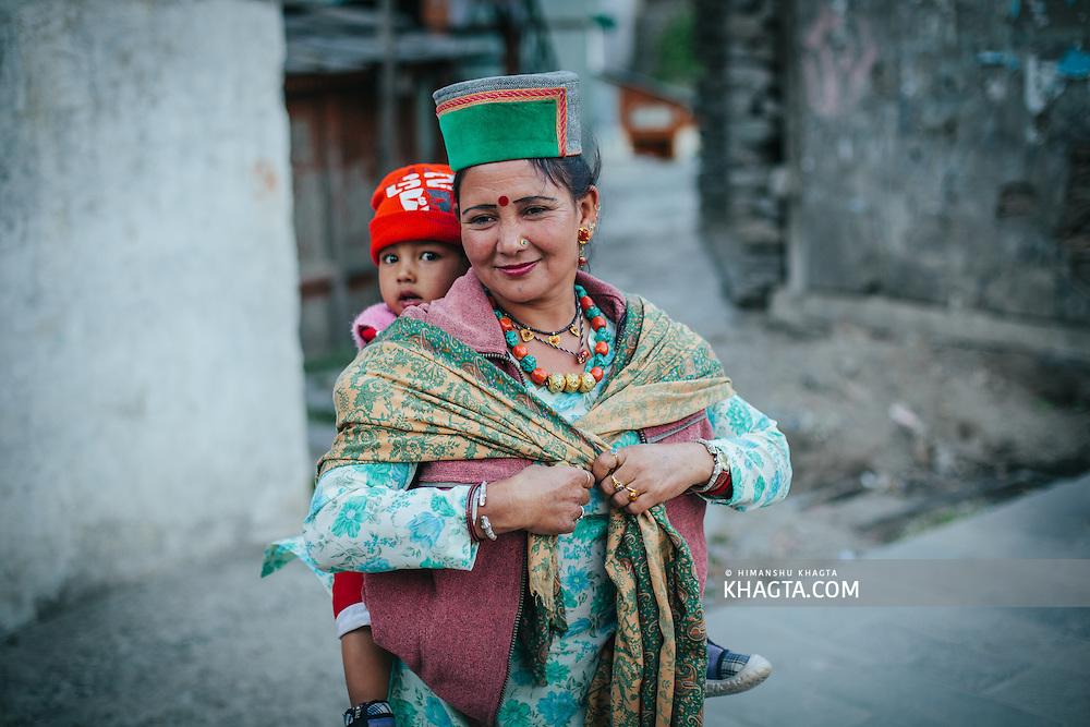 A kinnauri lady carrying her child on her back at Kalpa Village, Kinnaur